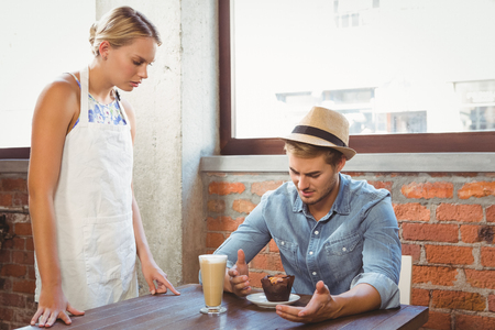 complaining: Handsome hipster complaining to blonde waitress at coffee shop