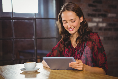 Smiling brunette having coffee and using tablet at coffee shop