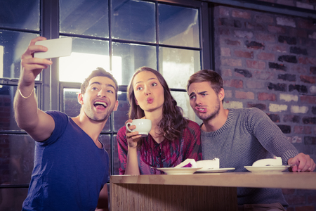 Grimacing friends taking selfies at coffee shop Stock Photo