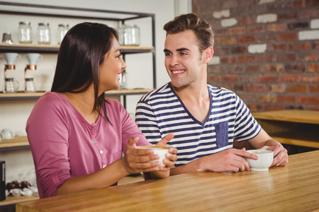 indian style sitting: Cute couple drinking a coffee together at a cafe Stock Photo