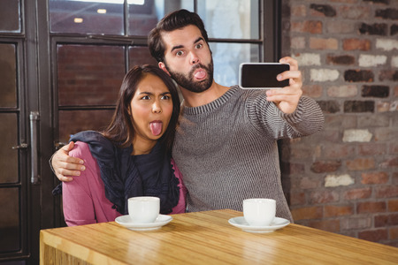 grimacing: Grimacing friends taking selfies at the cafe Stock Photo