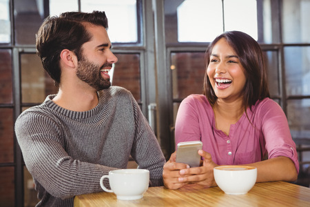 indian style sitting: Cute couple looking at a smartphone at a cafe
