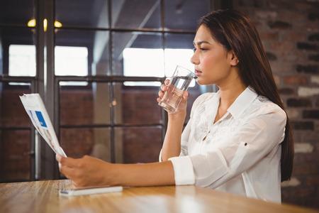 tomando agua: Casual businesswoman looking at files in a cafe Foto de archivo
