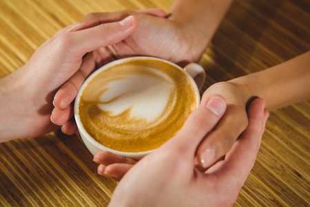 fashionable couple: Coffee with a heart with happy couple in the cafe Stock Photo
