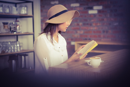 indian style sitting: Beautiful businesswoman reading a book outside at the coffee shop