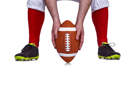 by placing: American football player placing the ball between his legs