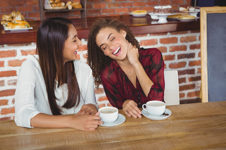 friendliness: Two smiling friends having coffee at coffee shop