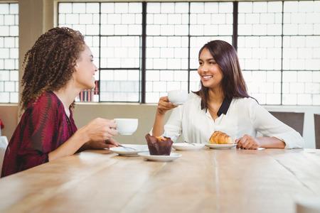 trato amable: Dos amigos sonrientes tomando un caf� en la cafeter�a Foto de archivo