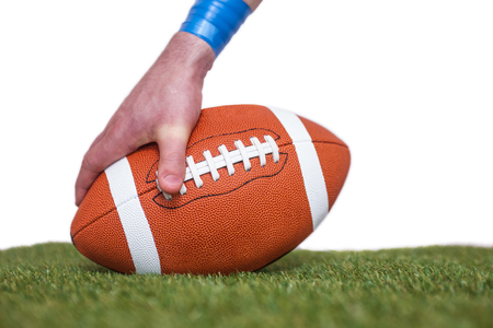 by placing: American football player placing the ball on the grass over a white background Stock Photo