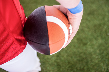 football on the field: American football player holding the ball on the field