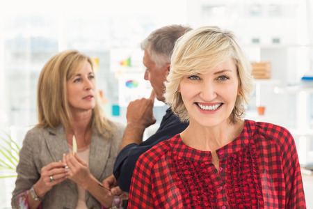 team from behind: Smiling businesswoman ahead with her team behind at office