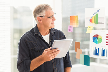Attentive businessman looking flow charts on the wall at office Stock Photo