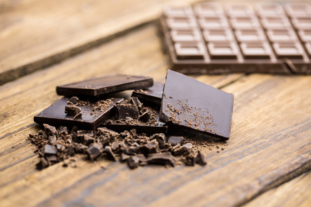 binge: Close up view of pieces of chocolate on a wooden table Stock Photo