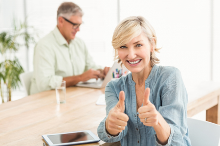 Portrait of a smiling businesswoman gesturing thumbs up at office