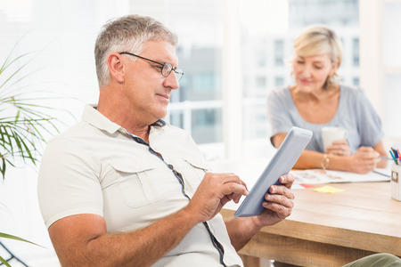scrolling: Side view of a serious businessman scrolling on a tablet at office Stock Photo