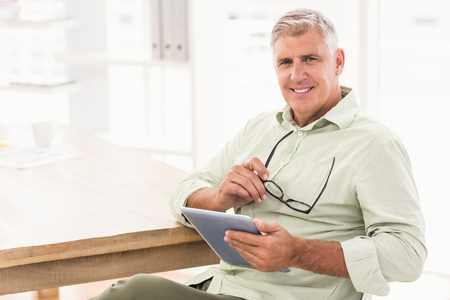 mature business man: Portrait of a smiling businessman holding a tablet at office Stock Photo