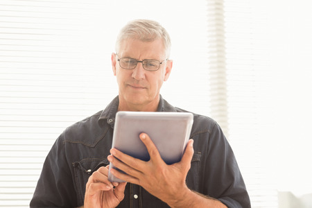 attentive: Attentive businessman scrolling on his tablet at the office