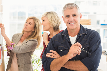 team from behind: Businessman with arms crossed with his team behind at office Stock Photo