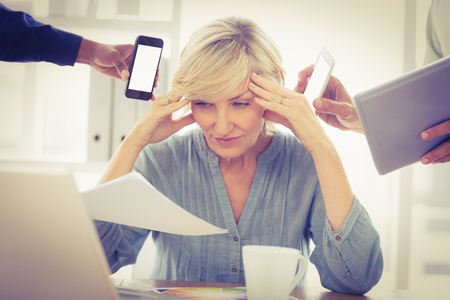 worked: Overwrought businesswoman with hands on head at the office Stock Photo