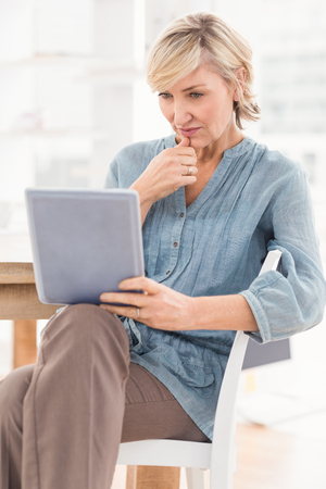 mature woman sitting: Thoughtful businesswoman looking at a tablet at the office Stock Photo