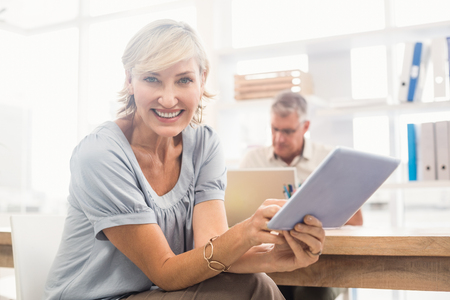 scrolling: Portrait of a smiling businesswoman scrolling on a tablet at office