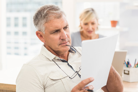 document: Attentive businessman reading an important document at office Stock Photo