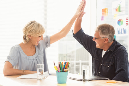 Happy business team doing a high-five together in the office Stock Photo