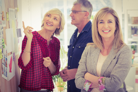 team from behind: Businesswoman with arms crossed with her team behind at office Stock Photo