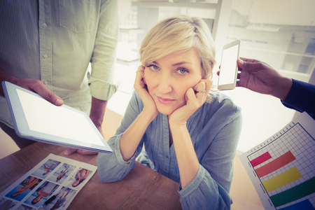 overwrought: Portrait of an overwrought businesswoman covering her ears at office Stock Photo