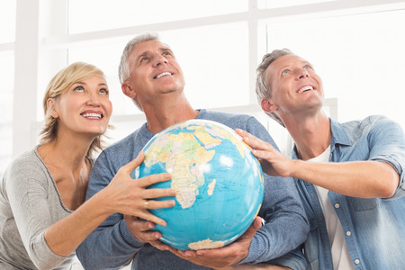 terrestrial globe: Happy business colleagues holding terrestrial globe and looking above