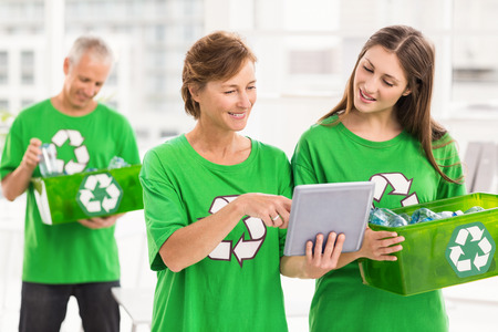 Eco-minded women with tablet and recycling box in the office