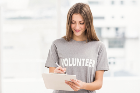 Lachende brunette vrijwilliger schriftelijk op klembord op kantoor