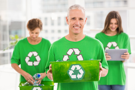 new business problems: Portrait of smiling eco-minded man holding recycling box in the office