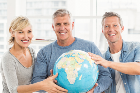 terrestrial globe: Portrait of business colleagues holding terrestrial globe at office