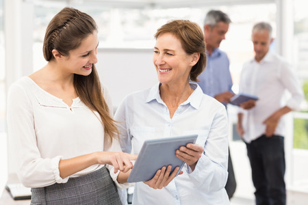 Smiling businesswomen using tablet in a meeting in the office