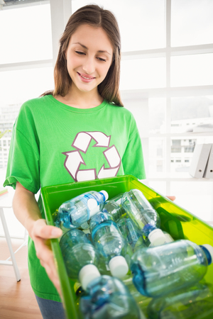 new business problems: Smiling eco-minded brunette showing recycling box in the office