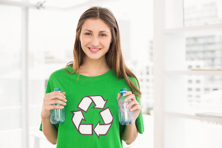 recycling bottles: Portrait of smiling eco-minded brunette holding recycling bottles in the office Stock Photo