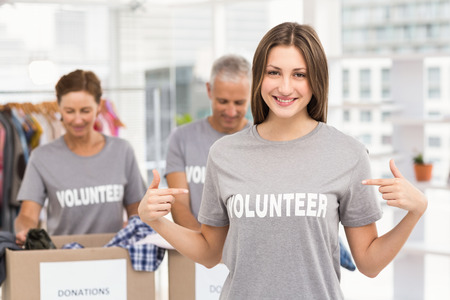 Portrait of smiling female volunteer pointing on shirt in the office Stock Photo