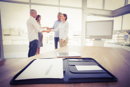 happy business team: Planner in front of handshaking business people in the office