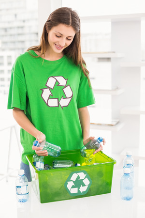recycling bottles: Smiling eco-minded brunette holding recycling bottles in the office Stock Photo