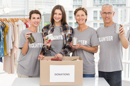 Portret van glimlachende vrijwilligers die schenkingen in het bureau tonen Stockfoto