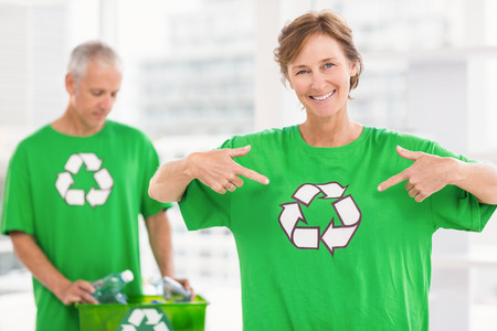 new business problems: Portrait of smiling eco-minded woman showing her recycling shirt in the office Stock Photo