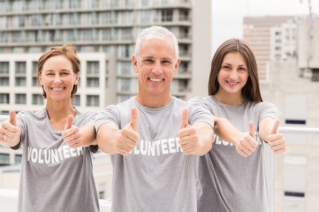 aide a la personne: Portrait of smiling volunteers doing thumbs up on roof of building