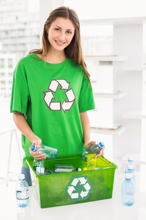 new business problems: Portrait of smiling eco-minded brunette holding recycling bottles in the office Stock Photo