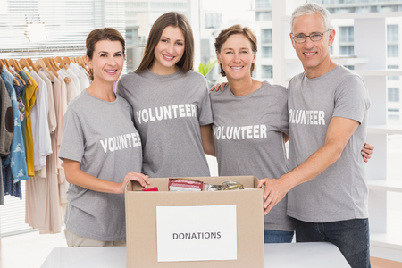 Portrait of smiling volunteers putting arms around each other in the office