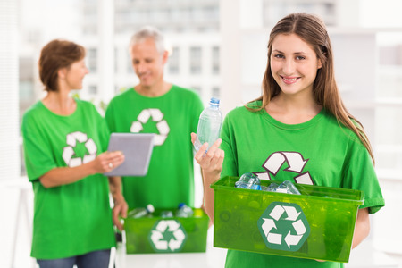 recycling bottles: Portrait of smiling eco-minded woman holding recycling box in the office Stock Photo