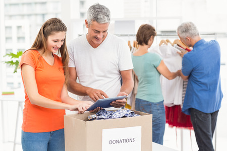 sorting: Smiling casual business people sorting donations in the office Stock Photo