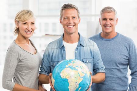 terrestrial globe: Portrait of a smiling businessman holding terrestrial globe at office