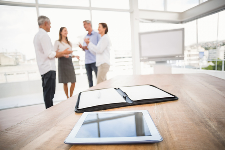 coworker: Tablet and planner in front of talking business people in the office Stock Photo