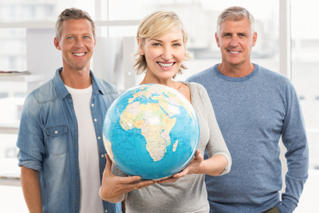 terrestrial globe: Portrait of a smiling businesswoman holding terrestrial globe at office Stock Photo